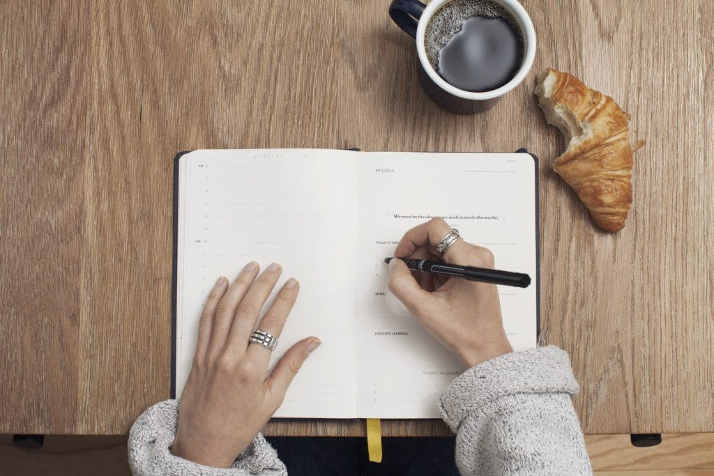 person writing in bullet journal with coffee and pastry